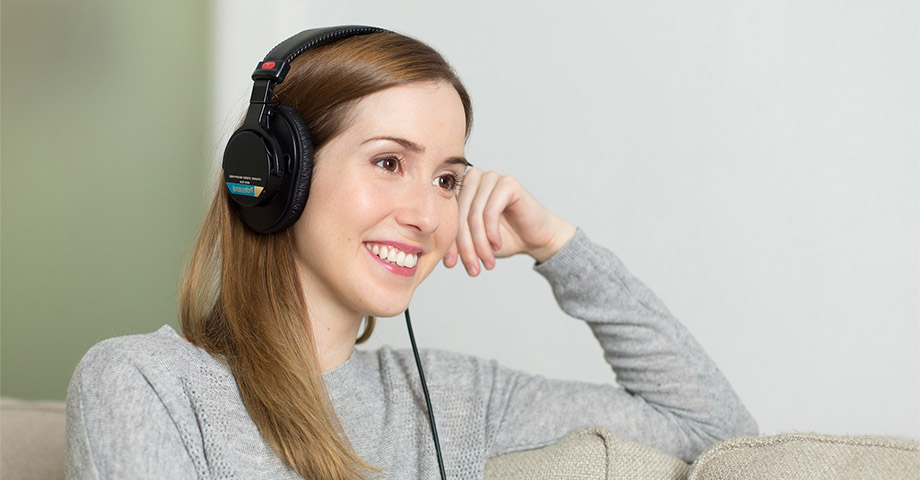 Young woman smiling sitting on a couch with headphones on